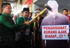 Datuk Seri Jamal Yunos using a sledge hammer on an effigy of Datuk Zaid Ibrahim at PWTC yesterday.