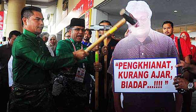 Datuk Seri Jamal Yunos using a sledge hammer on an effigy of Datuk Zaid Ibrahim at PWTC yesterday.