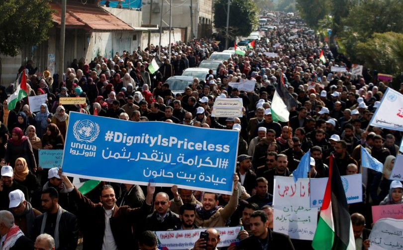 Palestinian employee of United Nations Relief and Works Agency (UNRWA) hold a sign during a protest against a U.S. decision to cut aid, in Gaza City