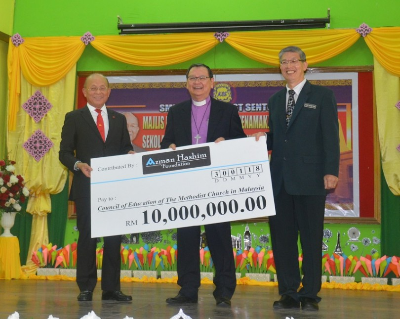 Azman (left) hands over the mock cheque to MCE representatives.