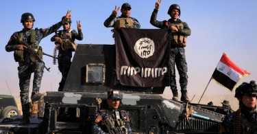Iraq's police turn the ISIS flag upside down after capturing part of a town from the group.