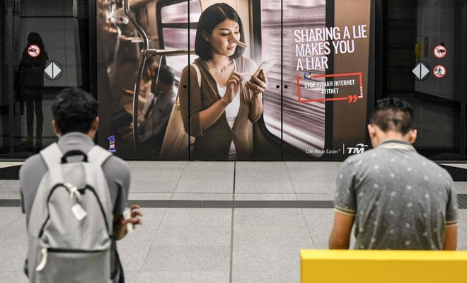 Commuters wait for a train in-front of an advertisement reading 'sharing a lie makes u a liar' at a station in Kuala Lumpur. (AFP)