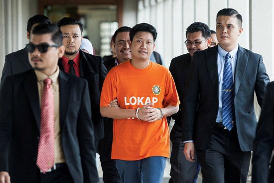 Adam (in orange T-shirt) being brought to court last year.
