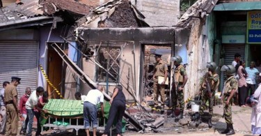 Sri Lanka's Special Task Force and Police officers stand guard near a burnt house after a Buddhist-Muslim clash in Digana, central district of Kandy.