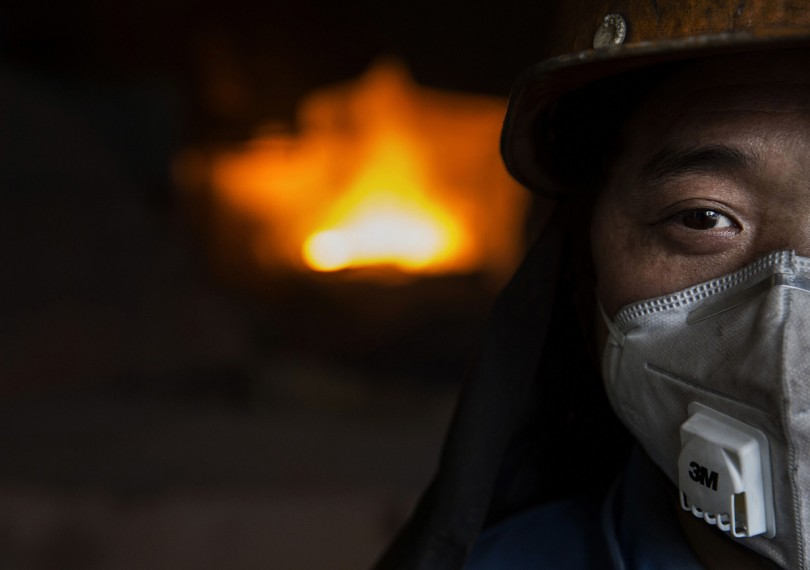 A Chinese worker stands near a furnace used for molten iron.