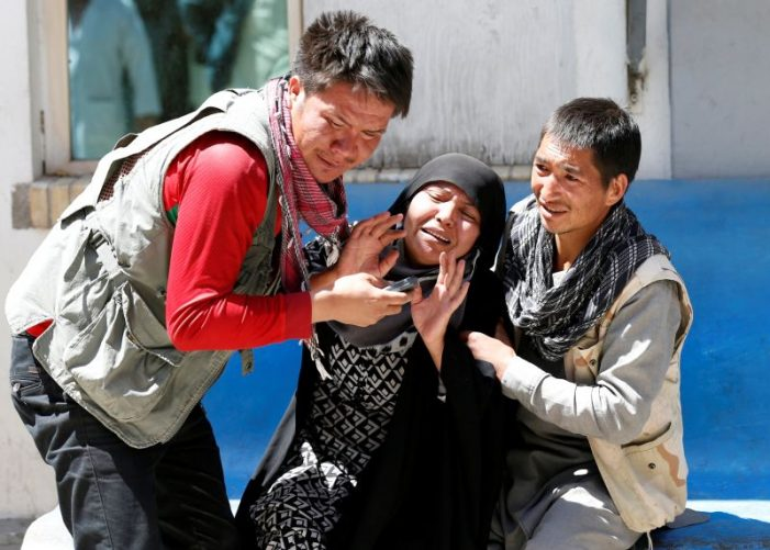 Relatives of victims mourn those killed by the blast at an election registration centre in Kabul yesterday.