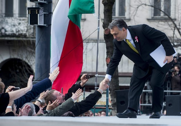 Hungarian Prime Minister Viktor Orban shakes hands with supporters after delivering a speech.
