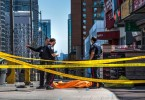 Police officers stand by a covered body in Toronto after a van mounted a sidewalk and crashed into a crowd of pedestrians  yesterday.