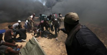 A wounded Palestinian demonstrator is evacuated as others take cover from Israeli fire and tear gas