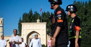 Police officers patrol the area as Muslims leave the Id Kah Mosque after the morning prayer in the town of Kashgar, in China's Xinjiang Uighur Autonomous Region,