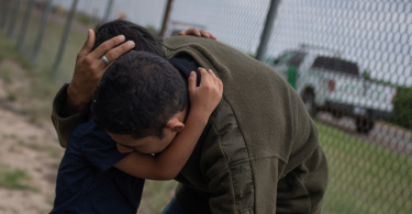 A four-year-old boy weeps in the arms of a family member as he and others were apprehended by border patrol agents after illegally crossing into the U.S. border from Mexico near McAllen, Texas, U.S., May 2, 2018.
