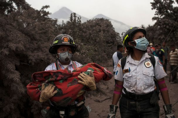 A firefighter carries the body of a child recovered near the Volcan de Fuego, or 'Volcano of Fire,' in Escuintla, Guatemala,