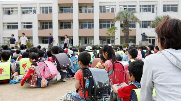 School children take shelter at schoolyard in Ikeda, Osaka, during the earthquake yesterday,