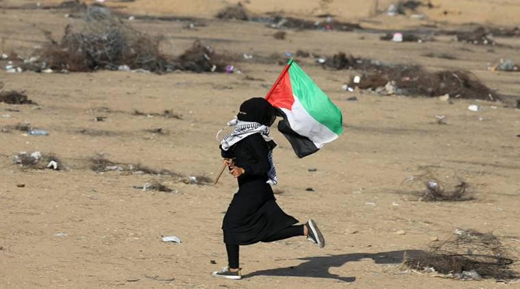A girl runs with a Palestinian flag during a protest at the Israel-Gaza border in the southern Gaza Strip.