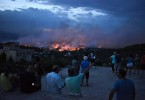 People watch a wildfire in the town of Rafina, near Athens, on Monday.
