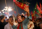 A supporter of Imran Khan wears a mask of the Pakistan Tehreek-e-Insaf leader during an election rally.