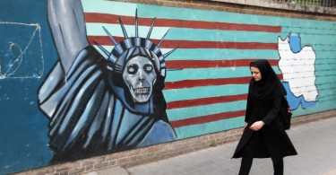 An Iranian woman walks past a mural on the wall of the former US embassy in Tehran.