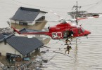 An aerial view shows a local resident being rescued from a submerged house by rescue workers using helicopter at a flooded area in Kurashiki,