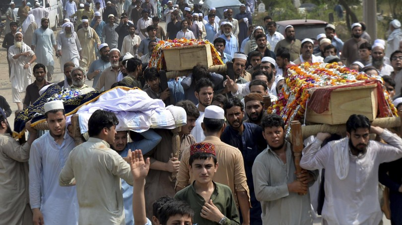 People carry the coffins of  victims of a suicide bombing at an election rally for burial in Peshawar