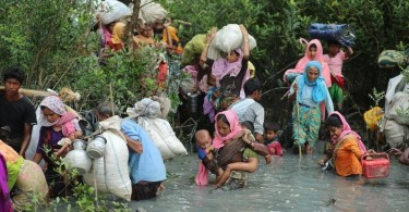 Rohingya Muslims walk through water after crossing the Myanmar border and Naff river to enter Bangladesh