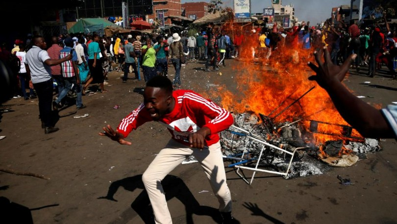 Supporters of the opposition Movement for Democratic Change party (MDC) of Nelson Chamisa react as they block a street in Harare on Wednesday.
