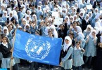 Palestinian schoolgirls in Gaza posing with a flag of United Nations Relief and Works Agency (UNRWA).