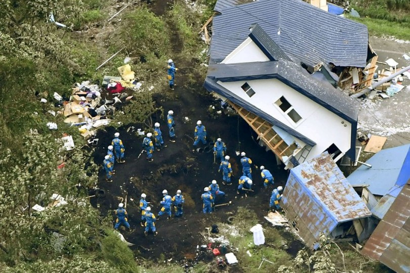 Rescuers search for survivors from a house damaged by a landslide caused by the earthquake in Atsuma, Hokkaido.
