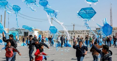 Students fly kites at a school for Palestinian children run by UNRWA. The kites bear messages which call for an end to the financial crisis that threatens their education.