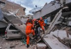 Search and rescue workers evacuate an earthquake and tsunami survivor trapped in a collapsed restaurant, in Palu.
