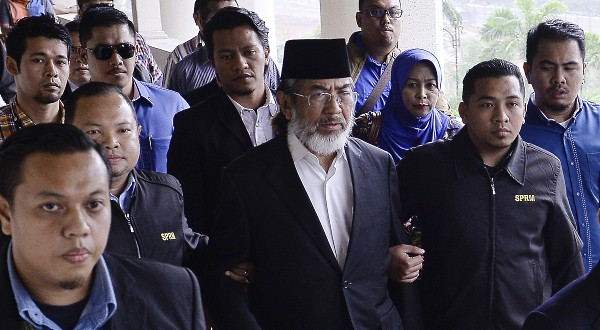 Musa (centre, with songkok) being taken to court.