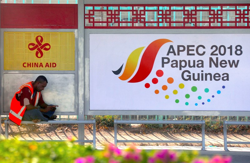 A local sits at a bus stop displaying a China Aid emblem and an Asia Pacific Economic Cooperation (APEC) banner in central Port Moresby, the capital city of Papua New Guinea,
