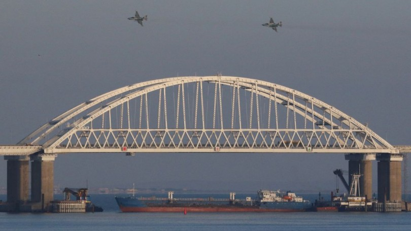 Russian jet fighters fly over a bridge connecting the Russian mainland with the Crimean Peninsula with a cargo ship anchored beneath it to block the Kerch Straits.