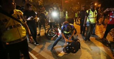 Police detain a man who failed to heed a warning to disperse near the Sri Maha Mariamman Devasthanam temple .