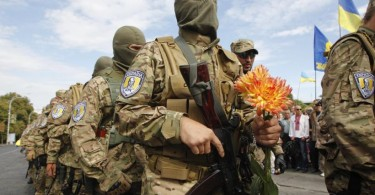 "A volunteer of the Ukrainian interior ministry's special battalion ""Sich"" holds flowers during a ceremony in Kiev."