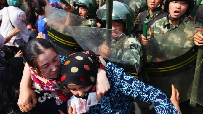 Uighur women during a protest in Urumqi against the detention of relatives by Chinese police.