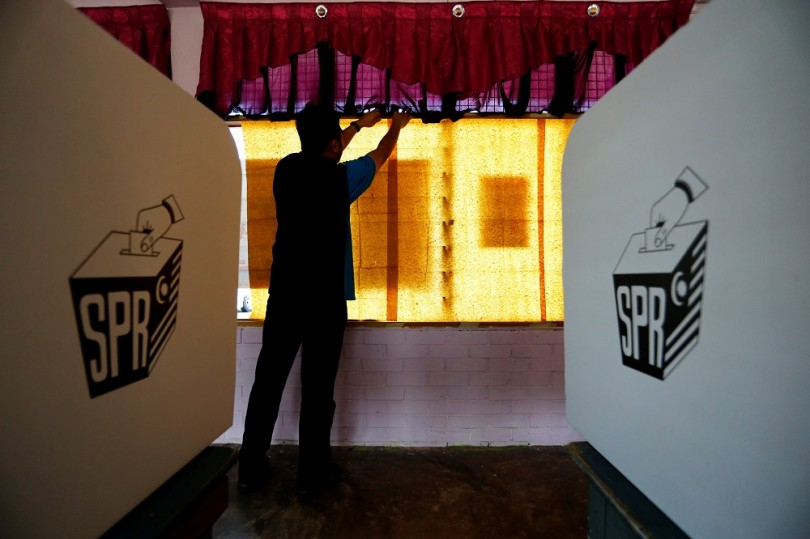 An election volunteer pastes sheets of paper on glass windows a day before the 14th general election at a polling station in Alor Setar