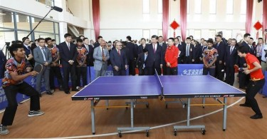 President Xi Jinping talks to table tennis coach Shi Zhihao while watching a training session with Peter O'Neill (second from Xi's right), prime minister of Papua New Guinea. The session between Zhang Yining, four-time Olympic gold medalist, and an athlete from PNG was at the new Butuka Academy. Xi and O'Neill attended the opening of the project financed and built by China.