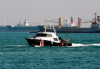 A Singapore Police Coast Guard vessel patrols lanes near freight ships at the republic's maritime border with Malaysia.
