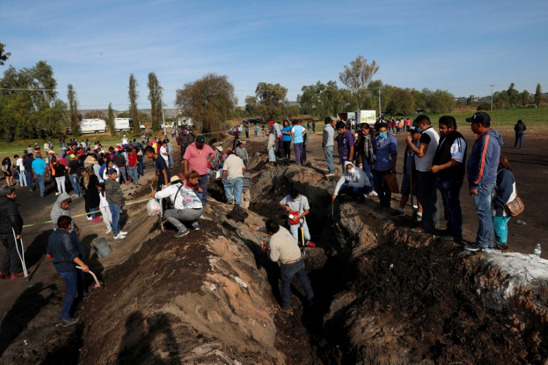 Residents search for human remains and items that could help to identify their missing relatives and friends at the site where a pipeline ruptured by oil thieves exploded, in the municipality of Tlahuelilpan, state of Hidalgo, Mexico