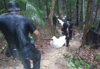 Malaysian policemen taking away the remains exhumed from the Wang Kelian graves.