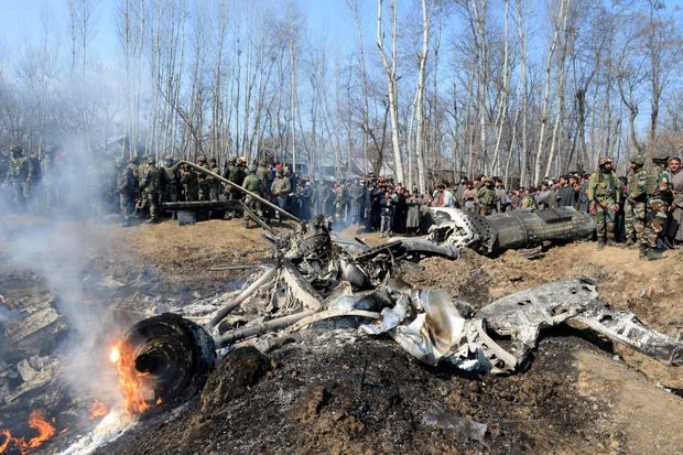 Indian soldiers and Kashmiri onlookers stand near the remains of an Indian Air Force aircraft after it crashed in Budgam district, some 30 kms from Srinagar, Kashmir.