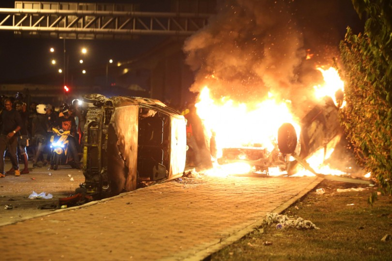 Motor vehicles parked by the road near the temple were torched during the rioting.