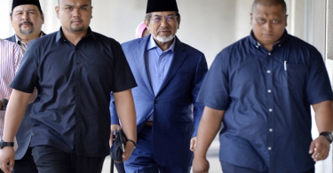 Musa (centre, with songkok) outside the courtroom.