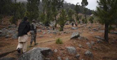 Pakistani reporters and soldiers checking the area near the targetted madrasa near Balakot, Khyber Pakhtunkhwa province, Pakistan.