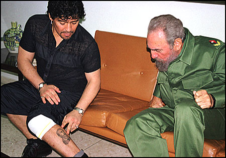 Maradona showing Castro the tattoo of the latter's face he has on his calf.
