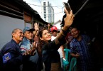 Shanti Ramchand, a candidate for the Indonesian election from Nasdem (National Democratic) party, takes a selfie with her supporters during her campaign trail at a hutment area south of Jakarta..