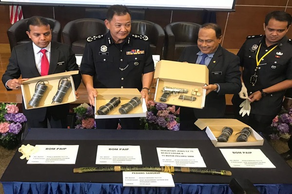 Hamid (second from left) and other officers with some of the items seized from the militants.
