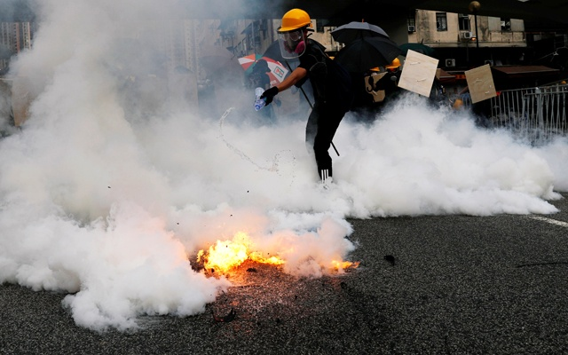 A demonstrator reacts to a tear gas during the protest in Yuen Long, New Territories, Hong Kong.