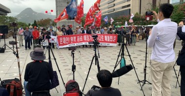 Mobile phones for a live broadcast film members of a conservative civic group taking part in a protest in Seoul,