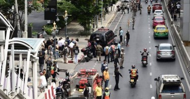 Onlookers and the police gather at the scene of one of the explosions in Bangkok.